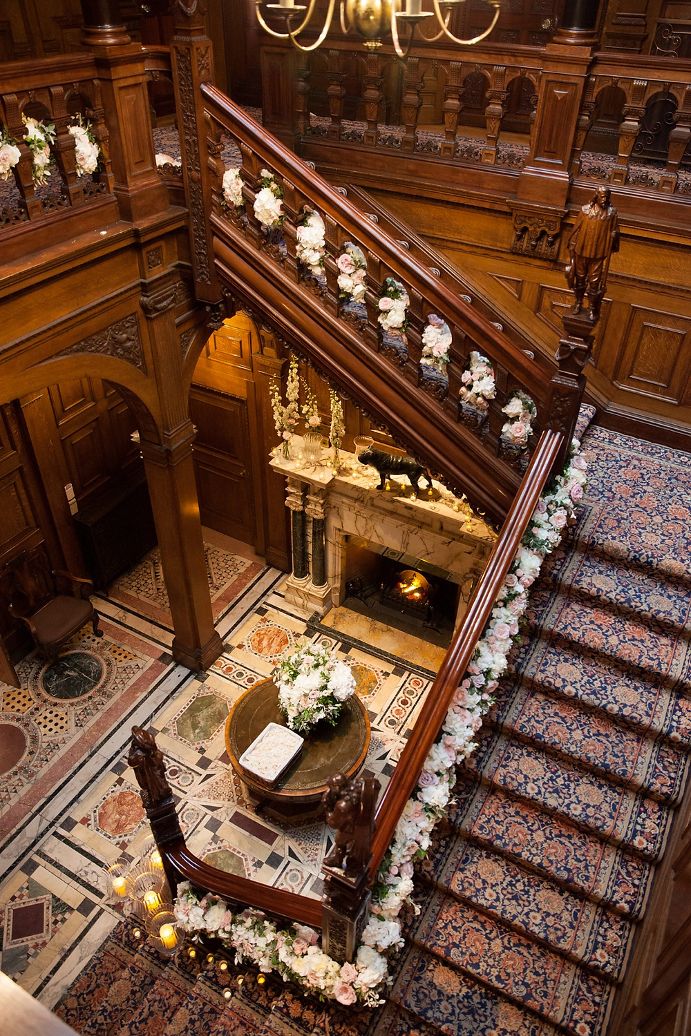 Shot from above showing mahogany staircase and floral installation of roses, peonies and orchids flowing down the sides of it