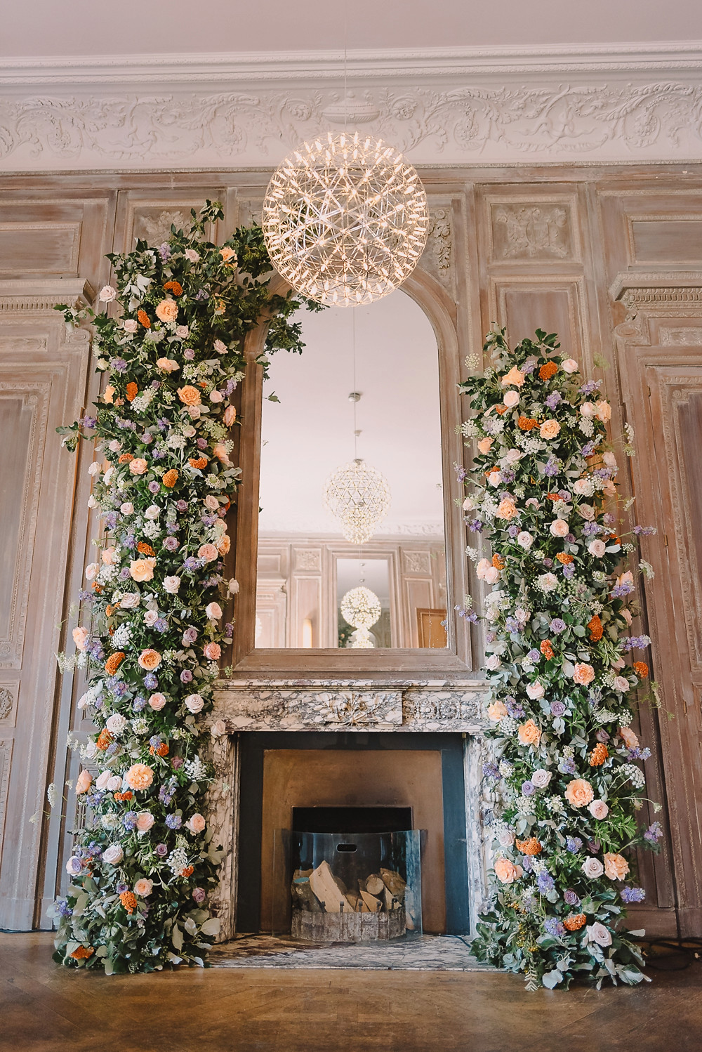 Large a-symmetric floral arch around fireplace at Cowley Manor