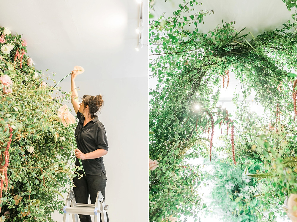 Luxury wedding florist Emma Soulsby up a ladder setting up a large floral installation including a jungle style tunnel