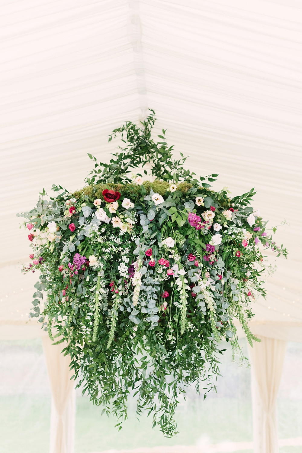 Hanging floral installation in a marquee. Foliage, roses and foxgloves in reds, whites and purples