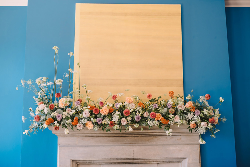 Purple and orange feature on mantelpiece against blue feature wall at Cowley Manor