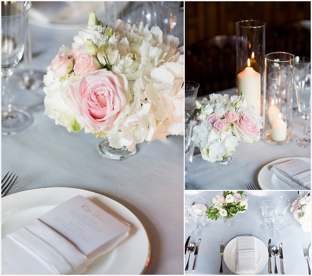 Table settings at Two Temple Place wedding. Candles and low vases of pale pink and cream flowers.