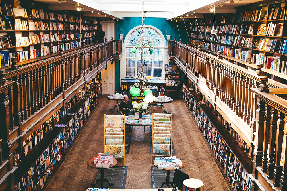 Large bookshop with turquoise wall and arched window