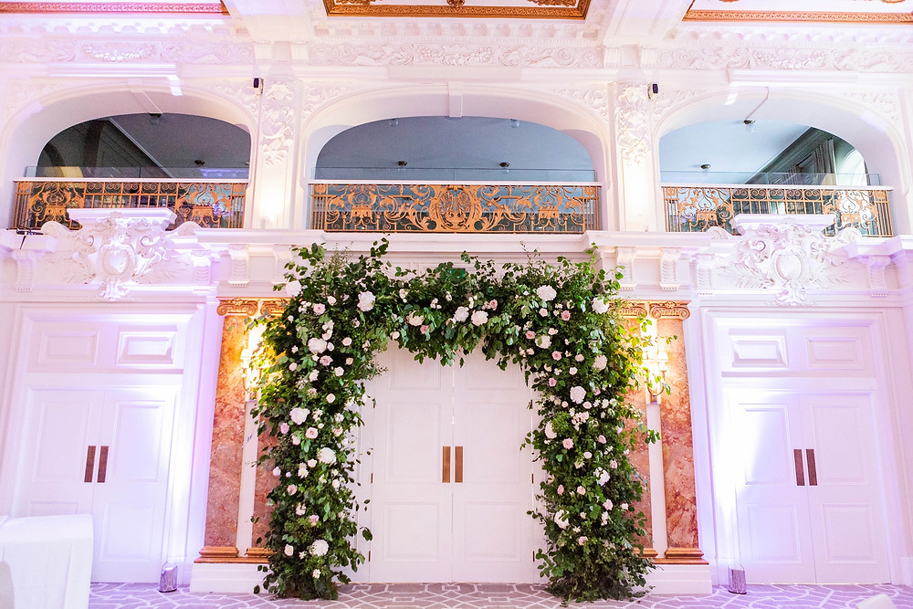 Huge floral arch with roses and hydrangeas across the double doors of the Kimpton Fitzroy's ballroom