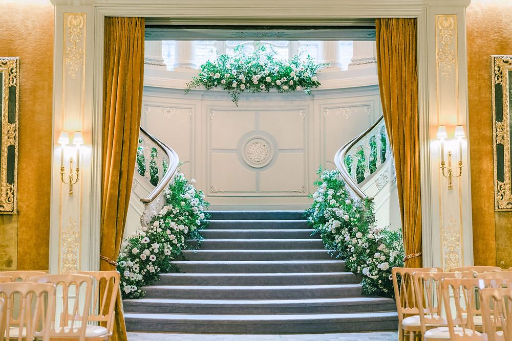 View of the Savile Club staircase adorned with flowers, shot through the doorway of another room and framed by gold velvet curtains.