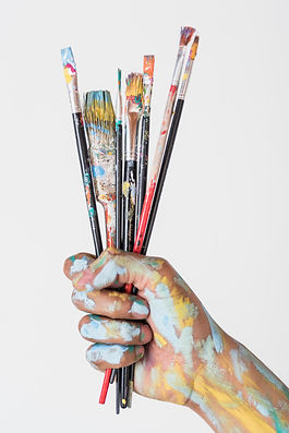 hand-holding-brushes-stained-with-paint.