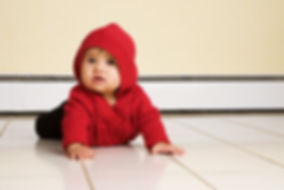 Baby girl crawling on white tile floor with beige tile