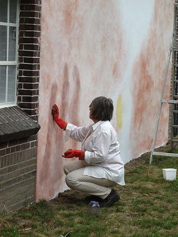 Aan het werk aan de muurschildering op de abdijwinkel.