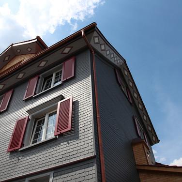 Rote Läden mit grauer Fassade