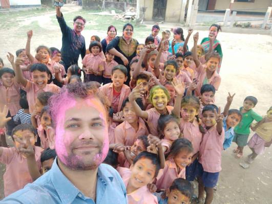 Fellows celebrating holi with children