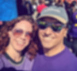 two smiling people wear purple shirts with a rally of activists behind them
