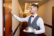 young-elegant-waiter-knocking-wooden-doo