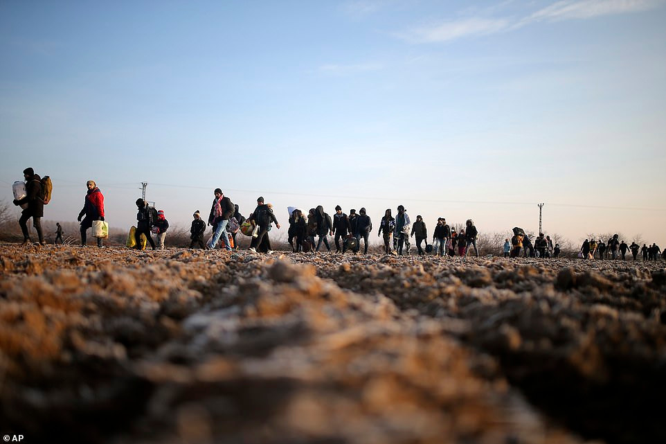 Rows of migrants pictured trudging through fields as they walk to reach Pazarakule at the Turkish border with Greece. Credits: Associated Press