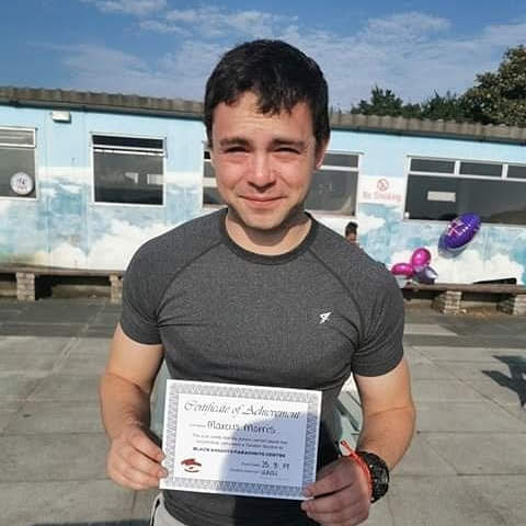I am holding a certificate of achievement after the skydive.