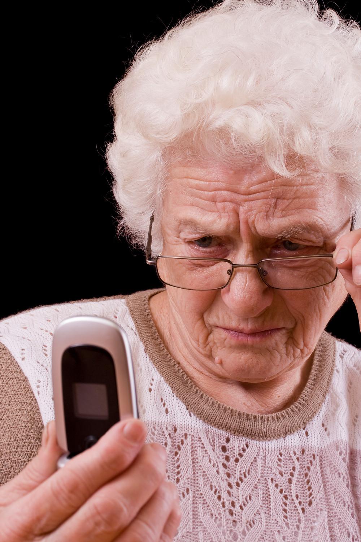 senior scams- older lady looking at phone