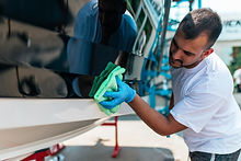 Boat maintenance - A man cleaning boat w