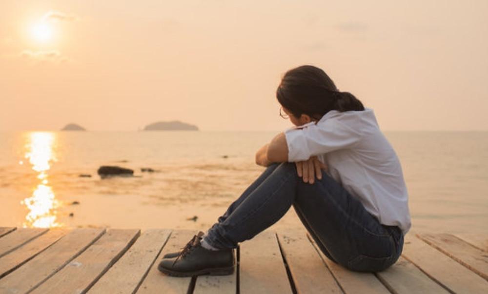 girl alone at beach at sunset
