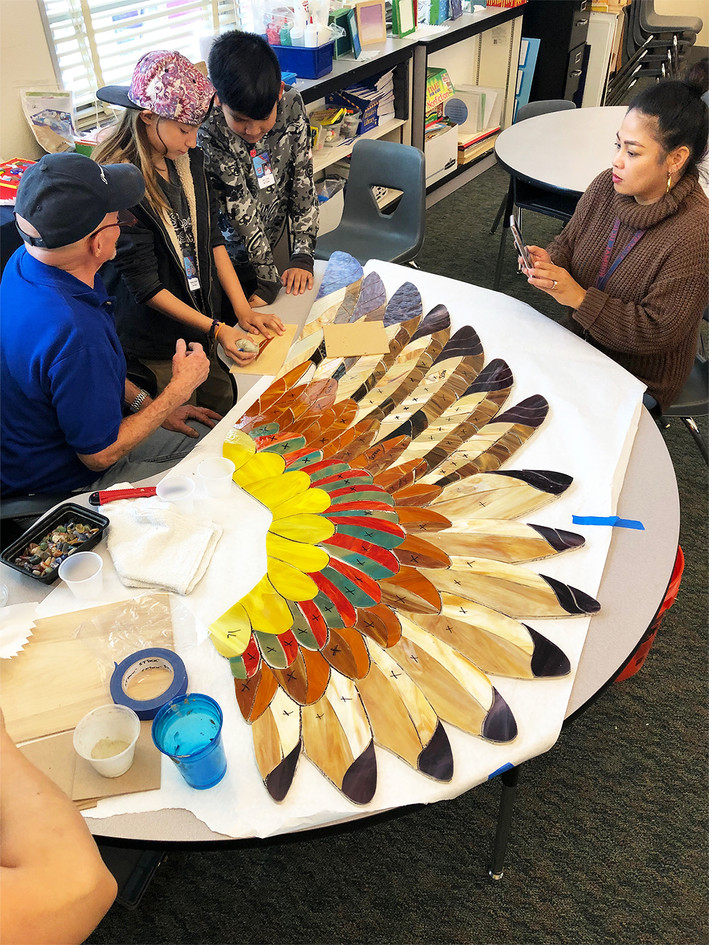 Students at work on the mosaic hawk wings