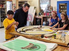 California state governor Gavin Newsom admiring the students' progress