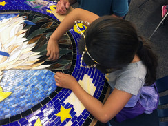 Students working on mosaic logo medallion