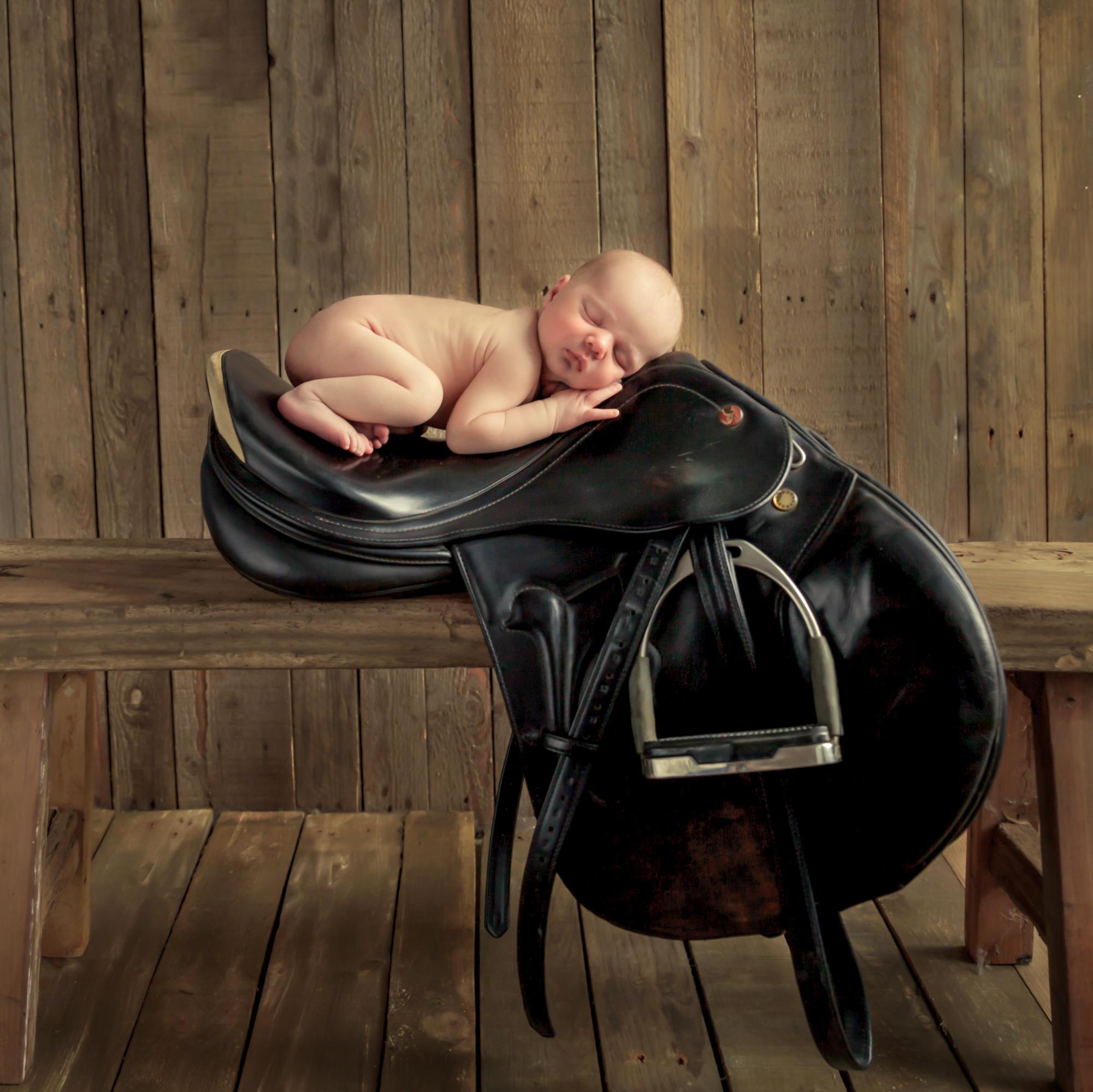 baby_op_zadel,paardrijzadel,