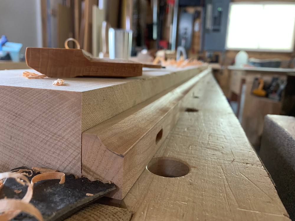 This image shows the end of the temporary maple sticking board and trim driven into the teeth of the planing stop. The concave profile has been cut into the trim. The quality of the cut is so clean that the surface is polished and is shining in the light from the shop window.