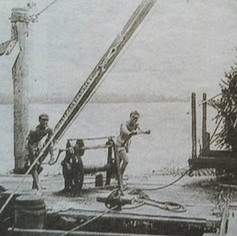 Cane harvesting. Boundary Creek. Using a hand winch to derrick sugar cane into cane barges on Garrett's Wharf in mid 1950s. The loaded cane was towed on teh Richmond River to the sugar mill at Broadwater.
