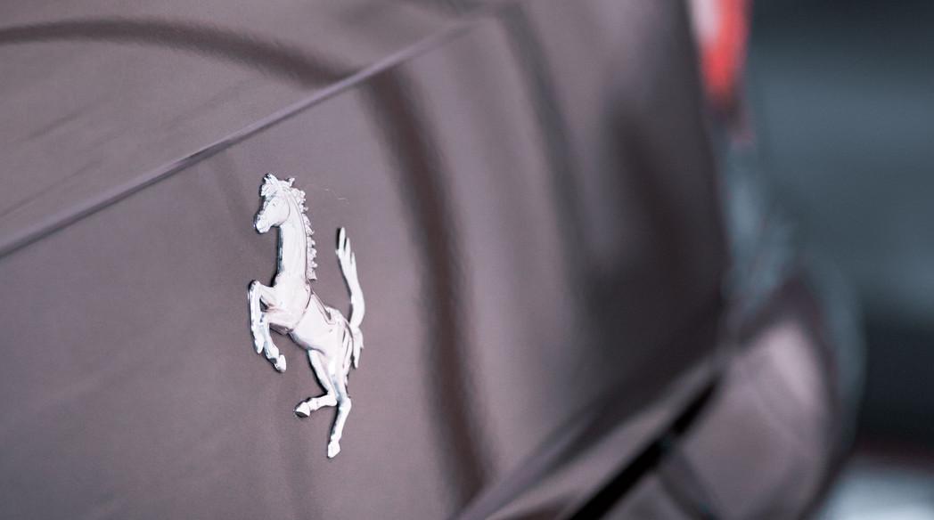 Back of a Ferrari next to an Aston Martin DB9 in an air chamber