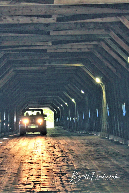 a car in covered bridge with sign.jpg