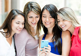 Group of girls looking at a cell phone.j