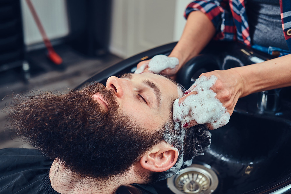 Professional hairdresser washing client hair in a barbershop.– stock image
