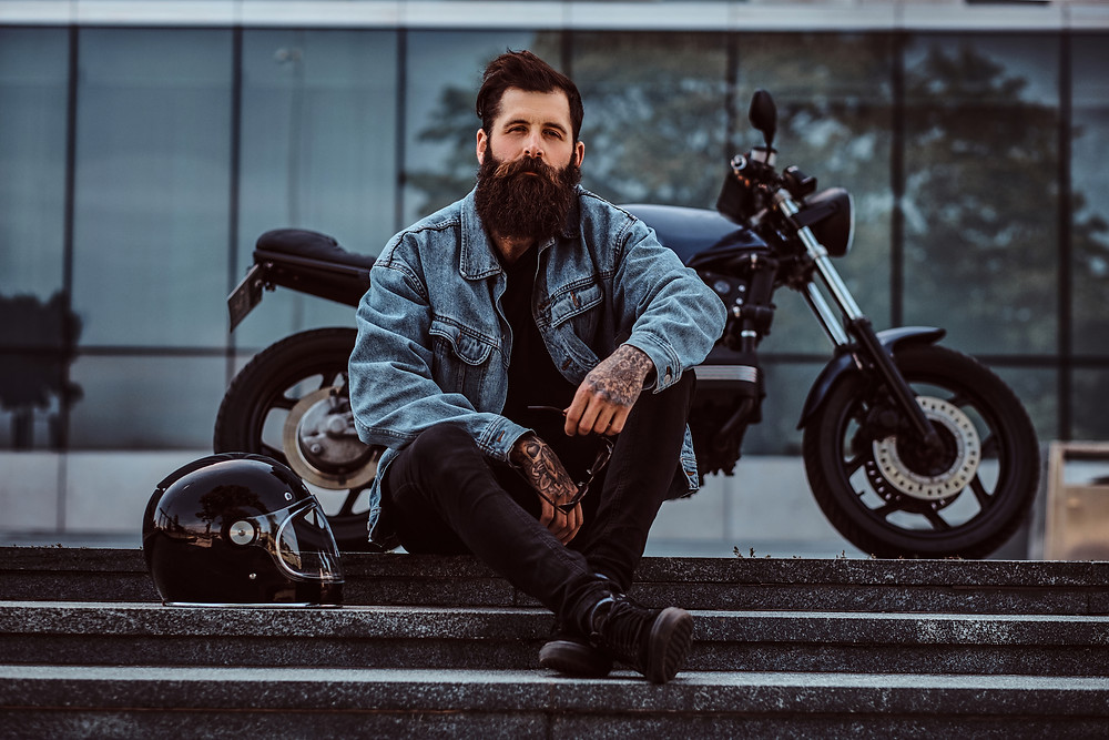 Portrait of a brutal bearded male dressed in a jeans jacket sitting on steps near his custom-made retro motorcycle against a skyscraper.– stock image