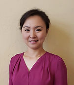Professional photo of Jingjing smiling. Purple shirt against off white background.