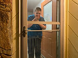 Nice looking young man looking out screen door and smiling