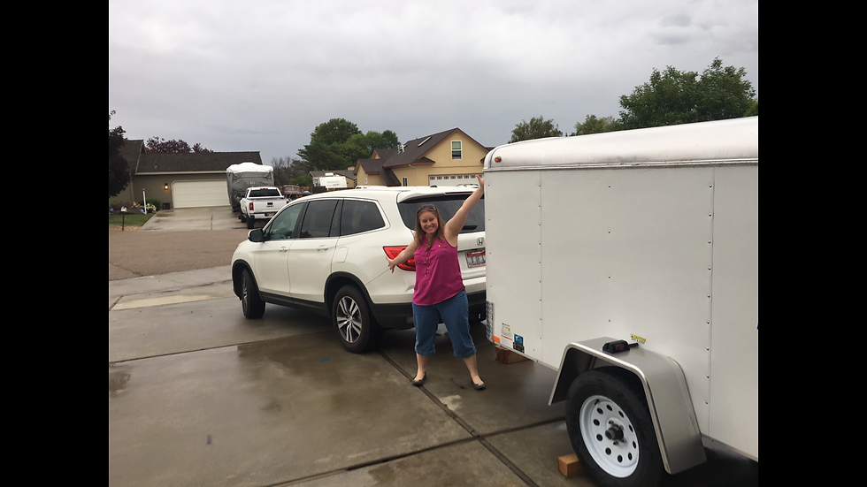 Dr. Brooke stands excited in front of white  Honda Pilot hooked to trailer