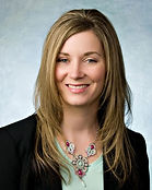 Professional photo of holly against faded blue background. Holly smiles  with hair down, suit jacket