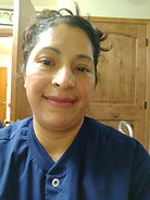 Carolina in clinic jacket smiling in front of a wooden door