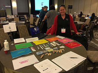 Dr. Brooke standing behind a table with rainbow colored papers and oral hygiene tools