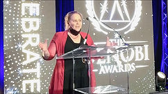 Dr. Brooke behind clear podium giving award acceptance speech