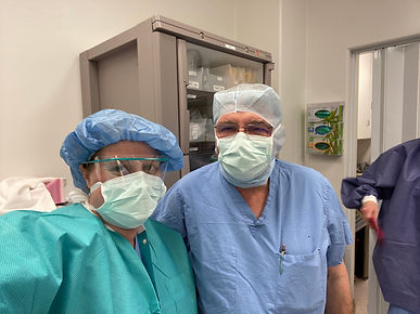 Dr. Brooke stands with Dr. McClusky in full operating room PPE