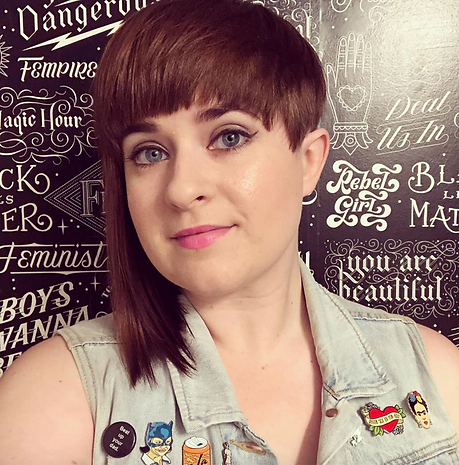 A photo of Whitney wearing a denim vest and enamel pins, taken at the Cards Against Humanity Theatre in Chicago.