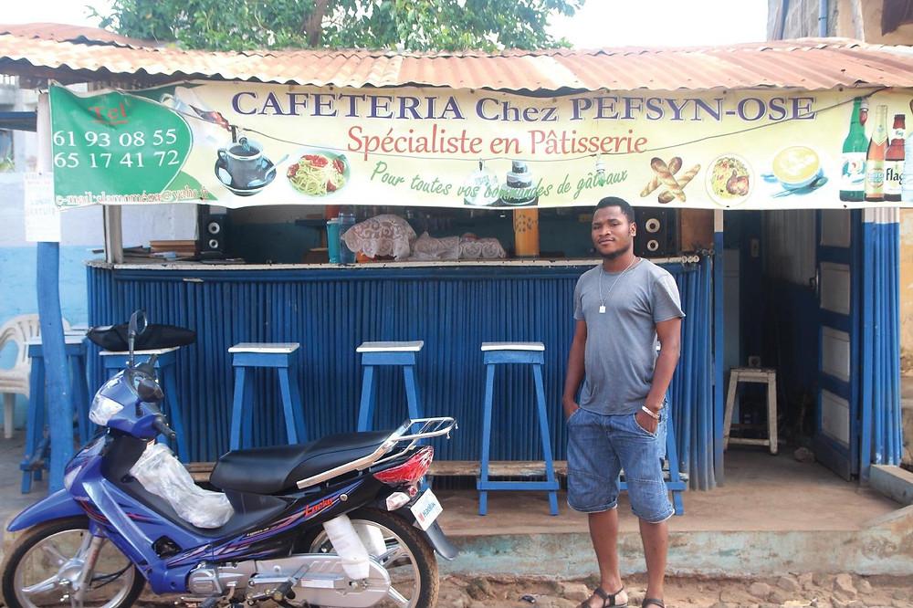 Le slameur béninois Pefsyn Ose pose devant sa cafétariat