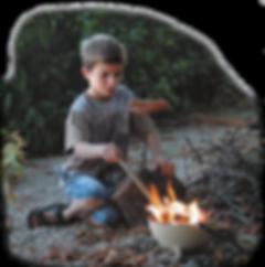 Junge bratat Wurst auf einer Feuerschüssel