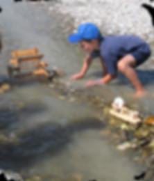 Junge mit Wasserrad am Fluss