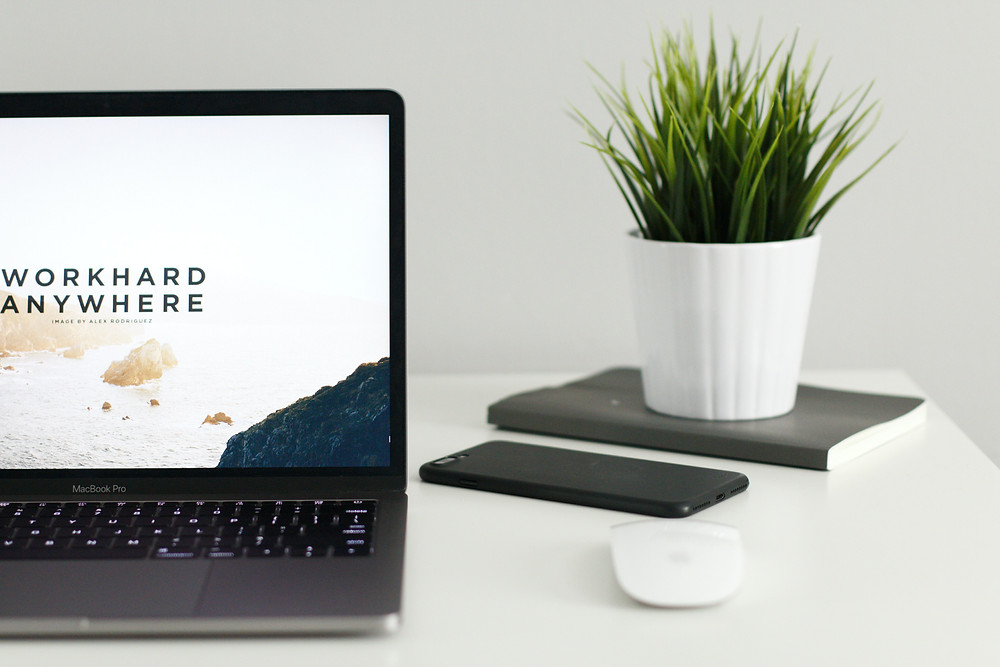 """White desk, computer, desk plant and quote on remote work saying """"work hard anywhere"""""""