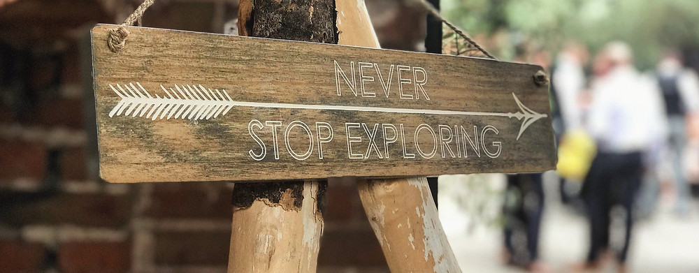 Motivational quote never stop exploring on wooden board