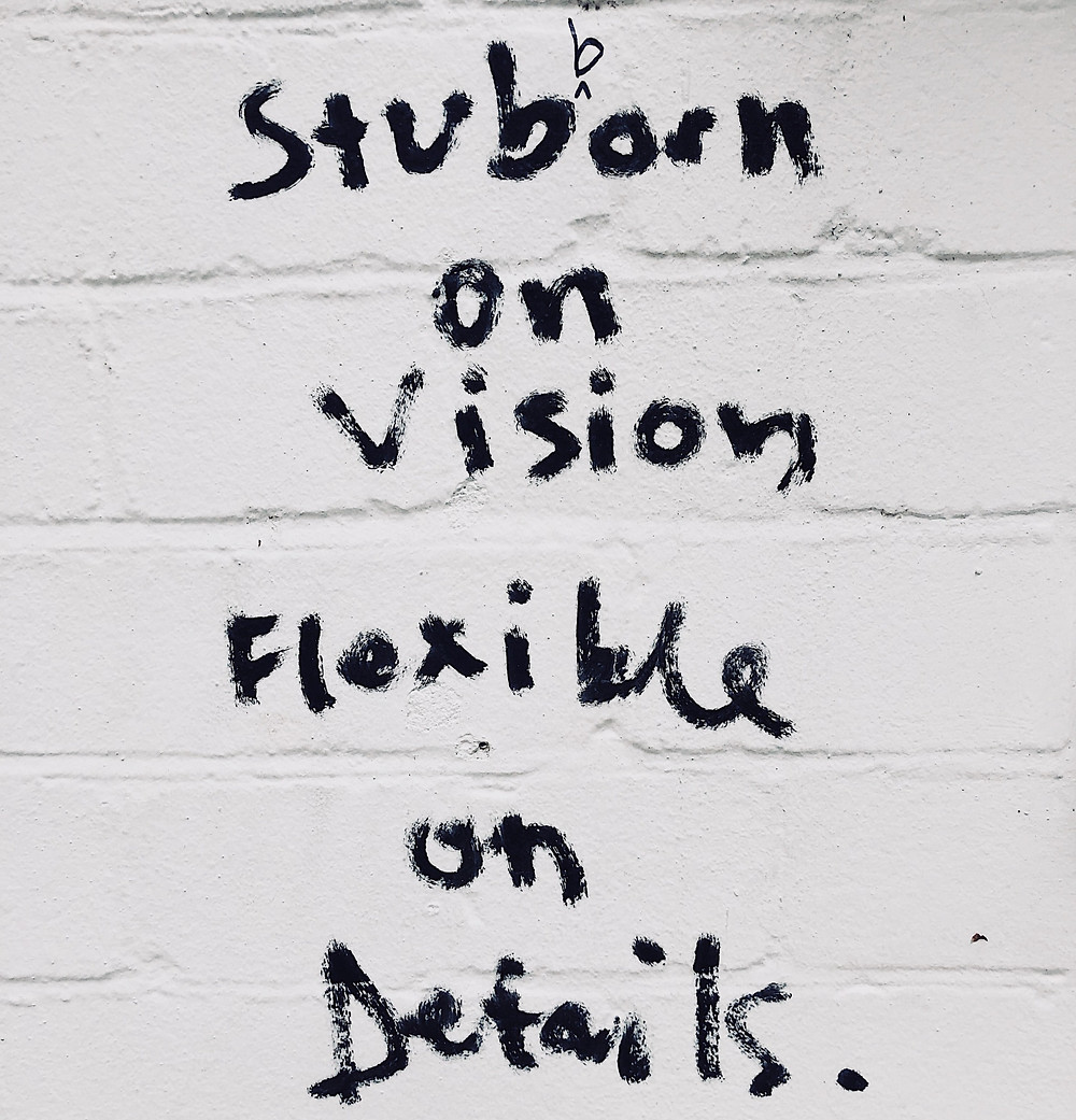 Inspiration quote about vision written in black paint on white brick wall