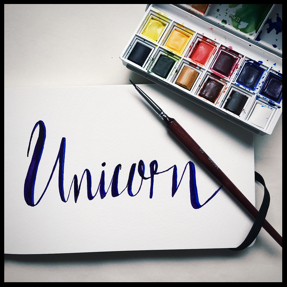 The word Unicorn written in watercolour calligraphy.
