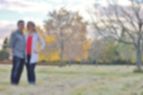 couple standing in a field in the fall.
