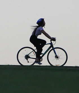 woman%20riding%20bike%20atop%20of%20hill